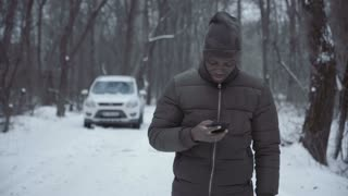 Black man on remote snowy road calling for help using phone having car engine breakdown.