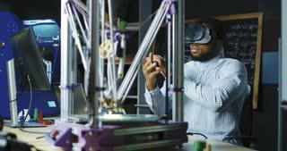 Black man wearing VR goggles and creating virtual model working in scientific lab.