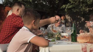 Bored young boy feeling annoyed sitting at table on family reunion party