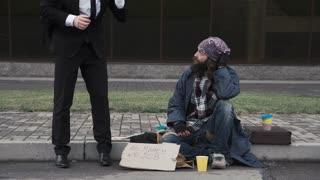 Broken businessman sitting down at beggar cheering him on city street
