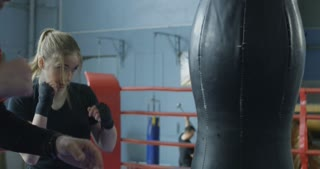 Brutal bearded man helping young sportswoman with boxing techniques training on ring.