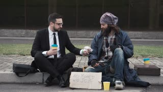 Businessman eating and talking with poor homeless man on pavement