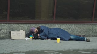 Businessman passerby giving money to sleeping homeless man