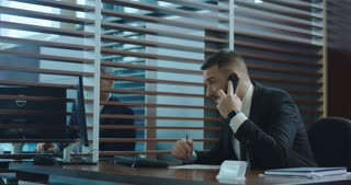 Businessman talking on phone in office and interacting with colleague while using computer and writing