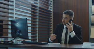 Busy adult agent in suit talking on phone while checking computer and writing in paper in office