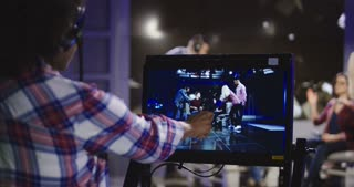 Casual African-American woman in headset controlling process of shooting TV show standing in front of computer screen and watching record