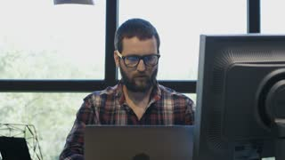 Casual bearded man taking glasses off and stretching back while sitting in chair at working desk with computer looking tired