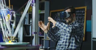 Casual man wearing VR goggles and creating virtual model working in scientific lab. Movement 4K shot on Red cinema camera.