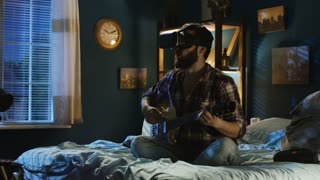 Casual man wearing VR goggles and give virtual concert with guitar while sitting on bed at home at night