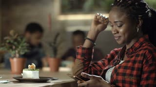 Casual pretty black girl using phone and enjoying dessert in cafeteria smiling at camera. 4K shot on Red cinema camera.