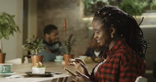 Casual pretty black girl using phone and enjoying dessert in cafeteria smiling at camera.