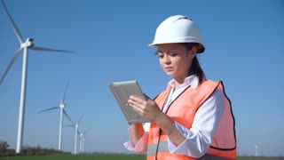 Caucasian female engineer wearing hard hat standing with digital tablet against wind turbine on sunny day and looking at camera smilingly