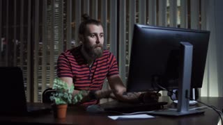 Cheerful bearded man in office smiling and typing on computer at night