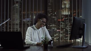 Cheerful black woman smiling and talking phone at computer in office in the evening