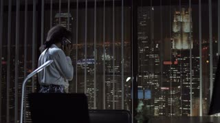 Cheerful black woman smiling and talking phone at window in office in the evening