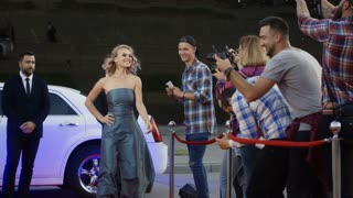Cheerful blonde woman in gray dress getting out of limousine on red carpet while bodyguards stop the fan