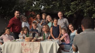 Cheerful family standing at table in garden and posing for photo
