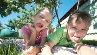 Cheerful girl and boy lying on grass in backyard and grimacing at camera showing tongues
