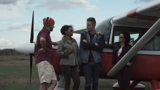 Close shot of group of young people talking next to small airplane outdoors