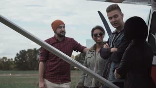 Close shot slow motion of group of young people talking next to small airplane outdoors