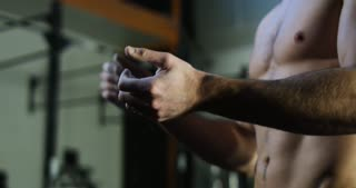 Close up view of confident muscular man applying white powder of magnesia on hands before weightlifting exercise.
