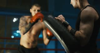 Close-up view of shirtless boxer kicking boxing bag in hands of trainer working out in gym and practicing Thai box.