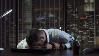 Close up view of tired businessman lying and sleeping on desk in office at night