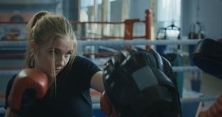 Close view from below of focused athletic woman in boxing gloves working out on technique while training with coach on ring.