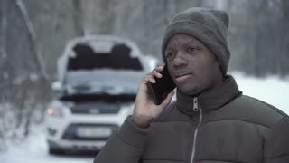 Close view of black man in winter jacket talking on smartphone standing on remote winter road with broken car.