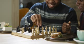 Close view of relaxing black men enjoying free time with refreshing coffee at table and playing chess in leisure.