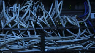 Closeup view of modern server computer with plenty of cables in rack with indicators blinking