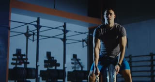 Concentrated sportsman doing hard exercise with heavy ropes while working out alone in dark gym. Shot on Red cinema camera.