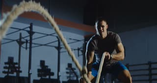 Concentrated sportsman doing hard exercise with heavy ropes while working out alone in dark gym.