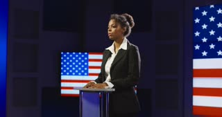 Confident African-American woman holding press conference while standing alone on podium with background of American flag on screen