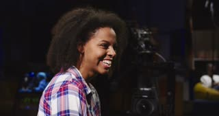 Confident African-American woman in casual shirt sitting in spotlight in telecasting studio and talking while presenting online show