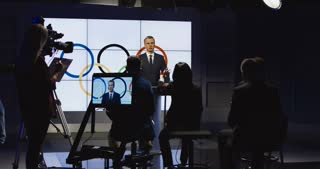 Confident representative in formal suit giving speech on press conference for Olympic Games standing on scene in front of camera