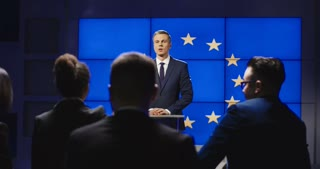 Confident representative of European Union giving speech and talking to journalists from stage on background of EU flag on screen