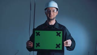 Construction worker young man in hard hat and safety goggles standing against blue wall with copy space holding tablet with green blank screen with cross for tracking