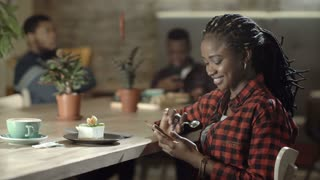 Content black woman in checkered shirt spending time in leisure looking relaxed while using phone. 4K shot on Red cinema camera.