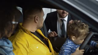 Content multiracial couple with son sitting in car and talking with dealer in auto shop giving credit card for payment to manager.