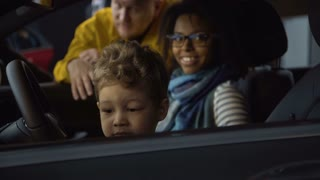 Content multiracial parents with boy exploring new car from inside making purchase in dealer shop.