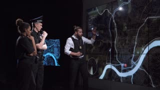 Coworking policemen watching GPS data on electronic map while spying bandit team and officers discuss response tactics in front of large live screens in a futuristic office