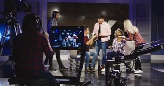 Crew in a production studio getting people ready to participate in an on stage discussion or interview with cameras in the foreground waiting to shoot