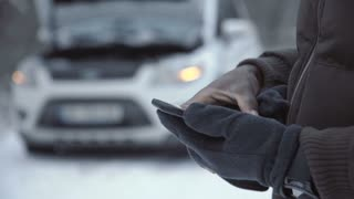 Crop shot of black man surfing smartphone standing outside with broken car in snows.