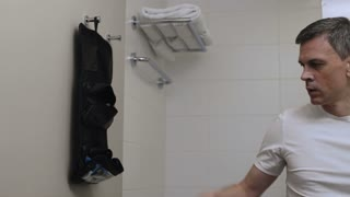 Crop view of businessman in trip taking grooming accessories out of toiletry travel kit in bathroom.