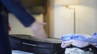 Crop view of man in elegant suit packing bag on bed preparing for traveling.