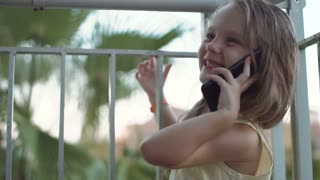 Cute little emotional girl talking phone at fence on balcony and smiling