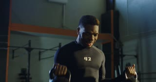 Determined African-American athlete working out in gym lifting two kettlebells training biceps.