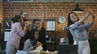Diverse happy coworkers eating pizza during break in office and taking selfie happily all together