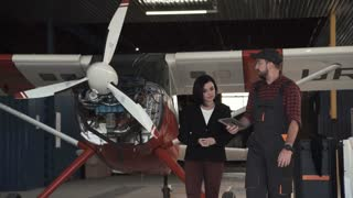 Draftswoman and technician standing near plane in aircraft workshop and talking with each other